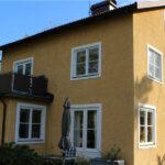 Kalkmålad fasadputs med vita fönsterfält.